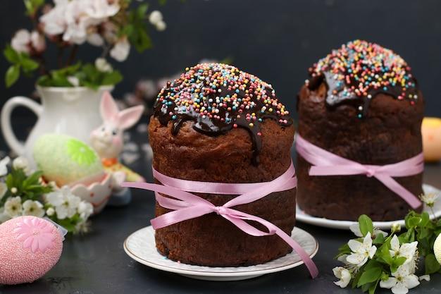 Natura morta con dolci pasquali ricoperti di glassa al cioccolato e uova colorate su fondo scuro