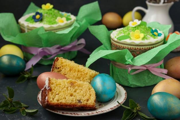 Natura morta con dolci pasquali in carta regalo e uova di pasqua multicolori su una superficie scura, in primo piano tagliare pezzi di torta pasquale, primo piano