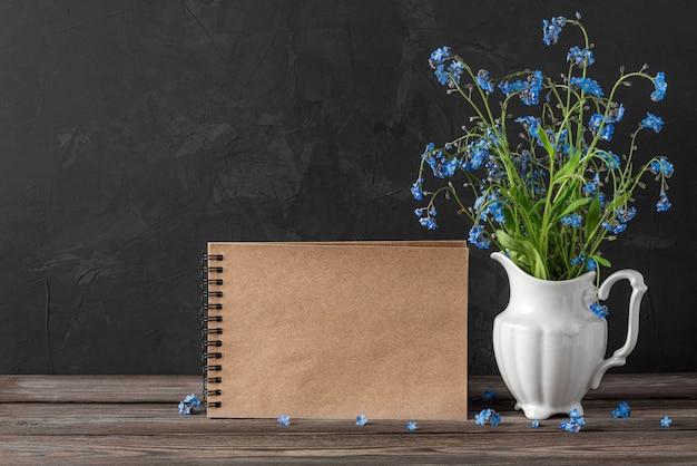 Natura morta con bouquet di fiori non ti scordar di me in vaso e cartolina d'auguri in bianco