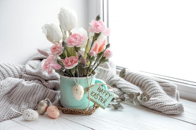 Natura morta con fiori freschi di primavera in un vaso, uova, una carta di pasqua felice e uno spazio di copia elemento lavorato a maglia.