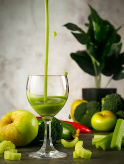 Natura morta con succo verde appena spremuto in un bicchiere. il succo viene versato in un bicchiere e le gocce sparse, sedano, verdure verdi e mele si trovano intorno. set di 3 succhi.