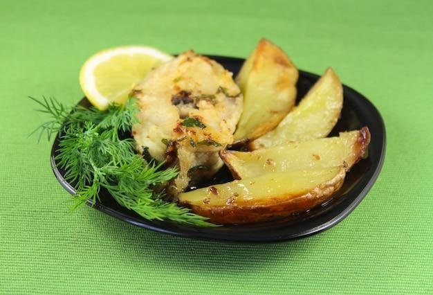 Natura morta con pesce fritto e patate al forno su un piatto da portata
