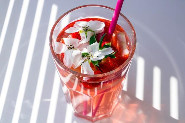 Natura morta con bicchiere di sangria alla fragola rinfrescante con spumante, fragola, cubetti di ghiaccio