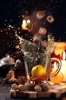 Natura morta con un bicchiere di tè che cade in un bicchiere con zollette di zucchero e schizzi di tè in direzioni diverse