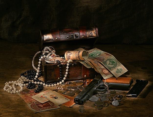 Natura morta con pistola, soldi, tesori, carte e scatola su uno sfondo scuro