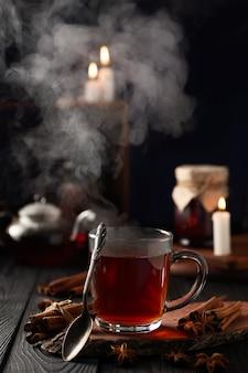 Natura morta con tè caldo in un bicchiere e vapore caldo che sale dal bicchiere
