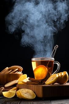 Natura morta con tè caldo e limoni, vapore denso sale sopra la tazza