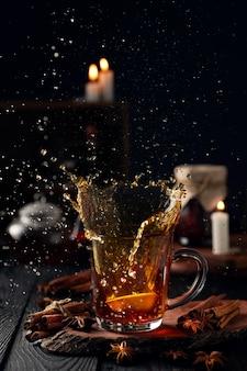 Natura morta con tè caldo con spezie al limone e una bella spruzzata da un bicchiere