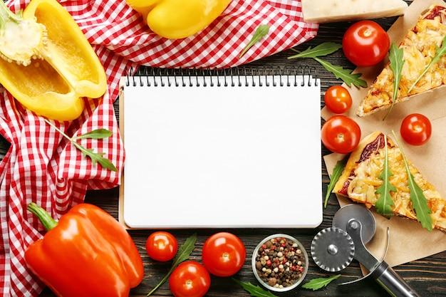 Natura morta con ingredienti per pizza e quaderno di ricette su tavolo di legno, vista dall'alto
