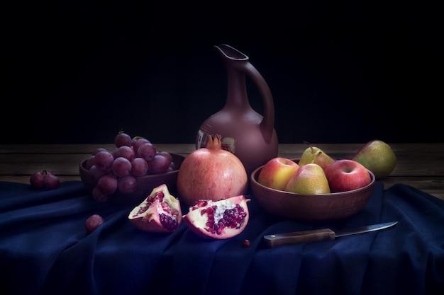 Natura morta con una brocca di vino, melograno, uva rossa, mele e pere su una tovaglia di lino blu scuro.