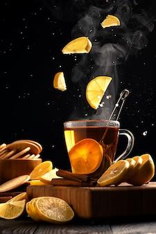 Natura morta con limoni che volano in una tazza di tè caldo, il vapore sale sopra la tazza