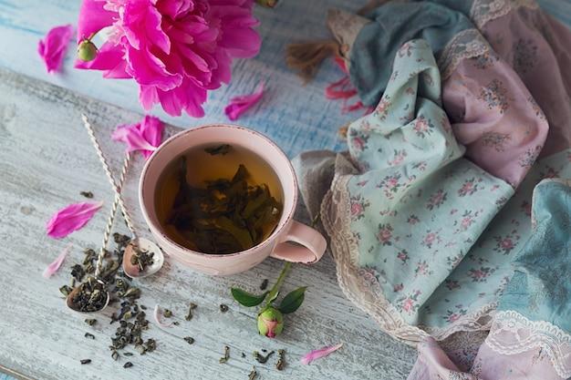 Natura morta con fiori di peonia rosa e una tazza di tè alle erbe o verde su fondo di legno rustico