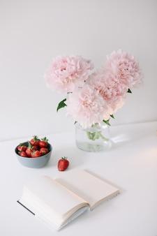 Natura morta con fiori di peonia rosa in un vaso, fragole fresche e un libro su un tavolo