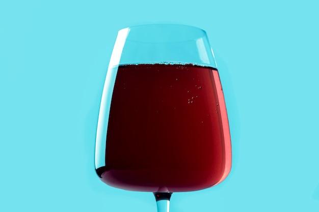 Natura morta con cocktail alcolico estivo rinfrescante rosso con fragole in bicchiere di vino su sfondo blu