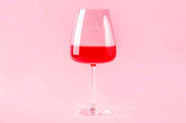 Natura morta con cocktail alcolico estivo rinfrescante rosso con fragole in bicchiere di vino isolato su sfondo rosa pink