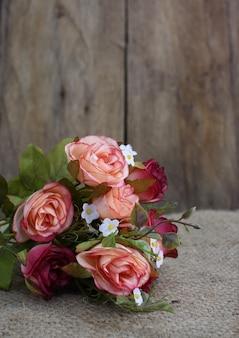 Natura morta con bouquet di fiori di rosa e spazio in legno