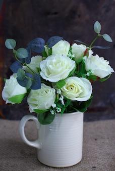 Natura morta con fiore rosa in vaso bianco su tela di sacco