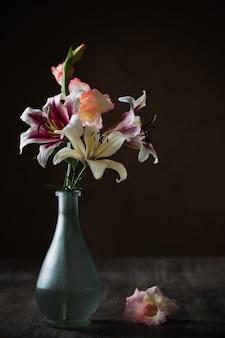 Natura morta con fiori estivi in vaso su oscurità