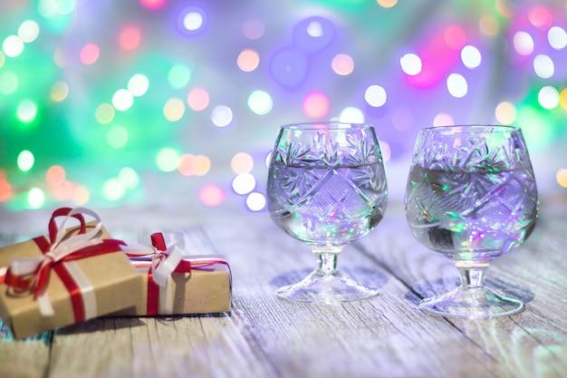 Natura morta con due bicchieri di champagne e scatole regalo con luci colorate nella parte posteriore