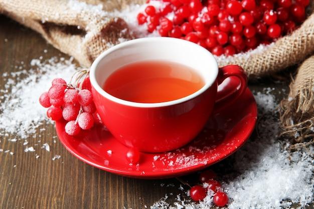 Natura morta con tè al viburno in tazza, bacche e neve, su un tovagliolo di tela di sacco
