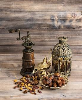 Natura morta con lanterna orientale vintage e mulino. uvetta e datteri su fondo di legno.
