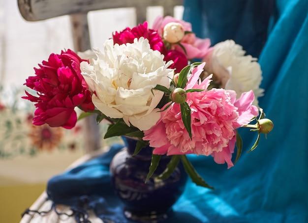 Natura morta con peonie bianche e rosa in un vaso blu su sedia vintaje