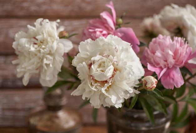 Natura morta con peonie bianche e rosa in un vecchio vaso di ceramica su fondo di legno
