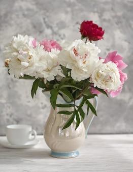 Natura morta con peonie bianche e rosa in vaso bianco