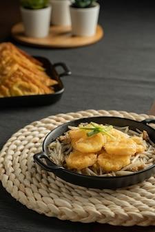 Germogli di soia saltati in padella e tofu all'uovo fritto ordinati in una piccola padella nera su una tovaglietta intrecciata