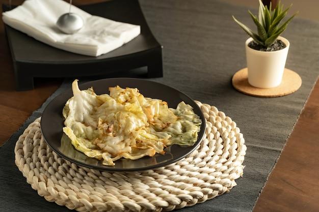 Cavolo saltato in padella con salsa di pesce servito in un piatto nero e decorare la tavola