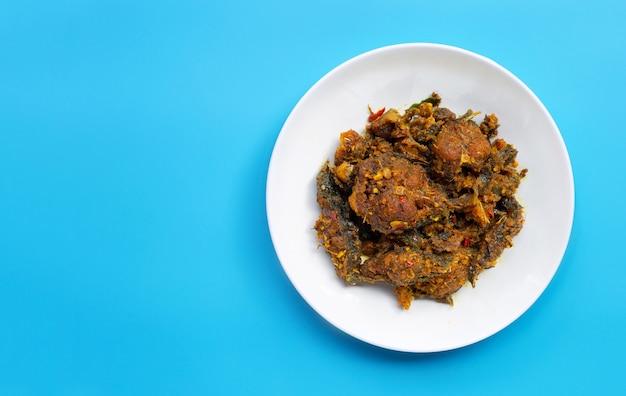 Mescolare pesce gatto fritto con pasta di curry su sfondo blu.