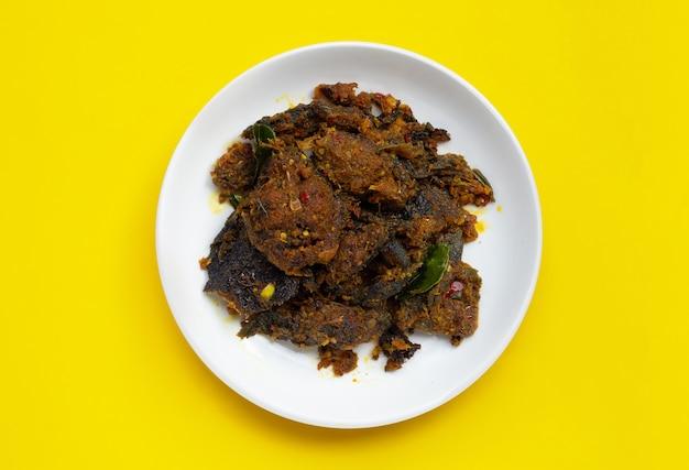 Mescolare pesce gatto fritto con pasta di curry su sfondo giallo.