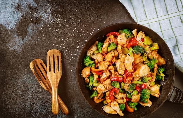 Pollo in padella con broccoli, peperone sulla superficie scura