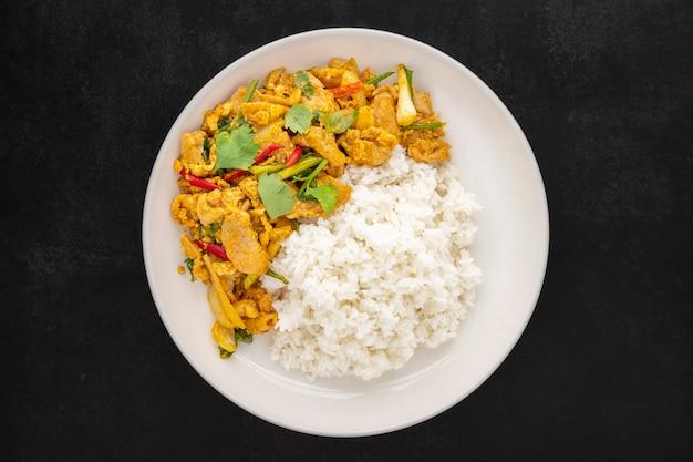 Pollo fritto in padella con polvere di curry accanto al riso al vapore in un piatto di ceramica semplicemente bianco su sfondo scuro, vista dall'alto, gai pad pong karee, cibo tailandese