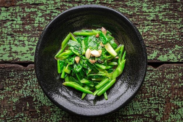 Cavoli saltati in padella con pesce salato e aglio in piatto di ceramica nera su fondo di legno vecchio verde, vista dall'alto, cavoli