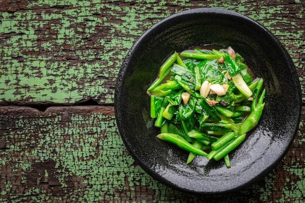 Cavoli saltati in padella con pesce salato e aglio in piatto di ceramica nera su fondo di legno vecchio verde con copia spazio per testo, vista dall'alto, cavoli