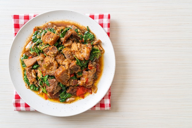 Pancetta di maiale croccante saltata in padella e basilico, cibo di strada locale asiatico