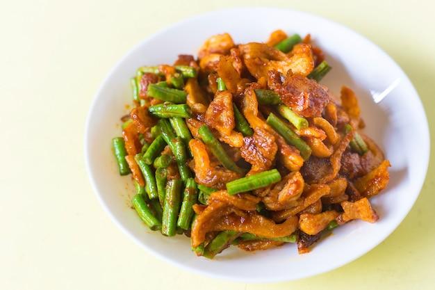 Maiale croccante fritto in padella e fagioli yardlong con pasta di curry piccante tailandese su piatto bianco in cibo tailandese