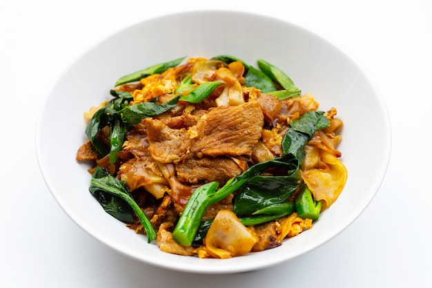 Mescolare i noodle piatti fritti e il maiale con salsa di soia.