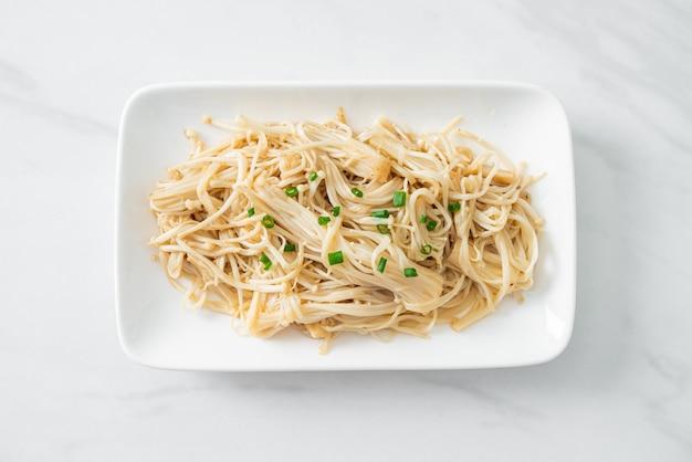 Funghi aghi dorati saltati in padella con burro su piatto bianco