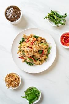 Mescolare basilico santo fritto con pesce ed erbe - stile di cibo asiatico