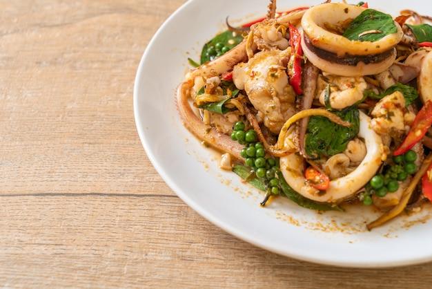 Mescolare basilico santo fritto con polpo o calamari ed erbe aromatiche - stile di cibo asiatico
