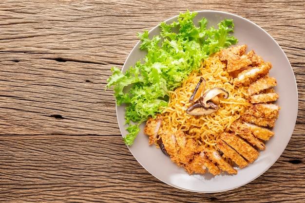 Spaghetti istantanei saltati in padella con cotoletta di maiale fritta giapponese o tonkatsu, lattuga e funghi shiitake su sfondo rustico in legno con copia spazio per il testo, vista dall'alto