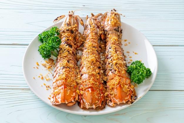 Mescolare le cicale di mare fritte con aglio sulla piastra bianca
