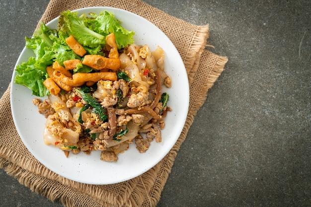 Noodle saltati in padella con pollo tritato e basilico - cucina asiatica