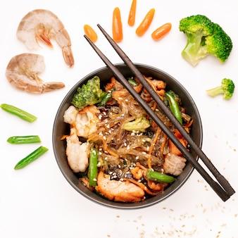 Mescolare le tagliatelle fritte con gamberi e verdure in un wok su sfondo bianco, vista dall'alto