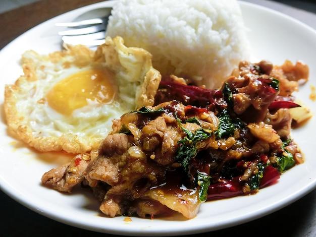 Maiale e basilico saltati in padella e uovo fritto con riso al vapore in un piatto bianco
