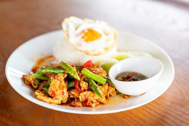 Mescolare il maiale fritto in pasta di curry rosso con riso e uovo fritto