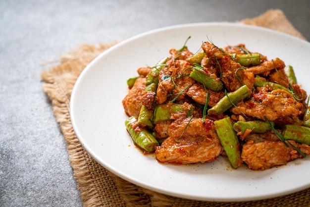 Mescolare il maiale fritto e la pasta di curry rosso con il fagiolo pungiglione