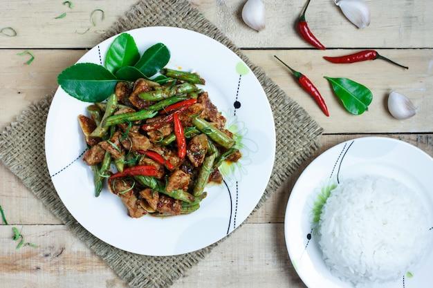 Mescolare la carne di maiale fritta e pasta di curry rossa con fagiolino